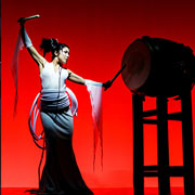 Asian lady performer ready to strike a barrel drum