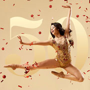 Lady dancer leaping in the air over a 50 year logo