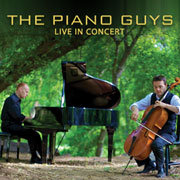 Two musicians: one playing a piano and the other play a cello in an outdoor setting