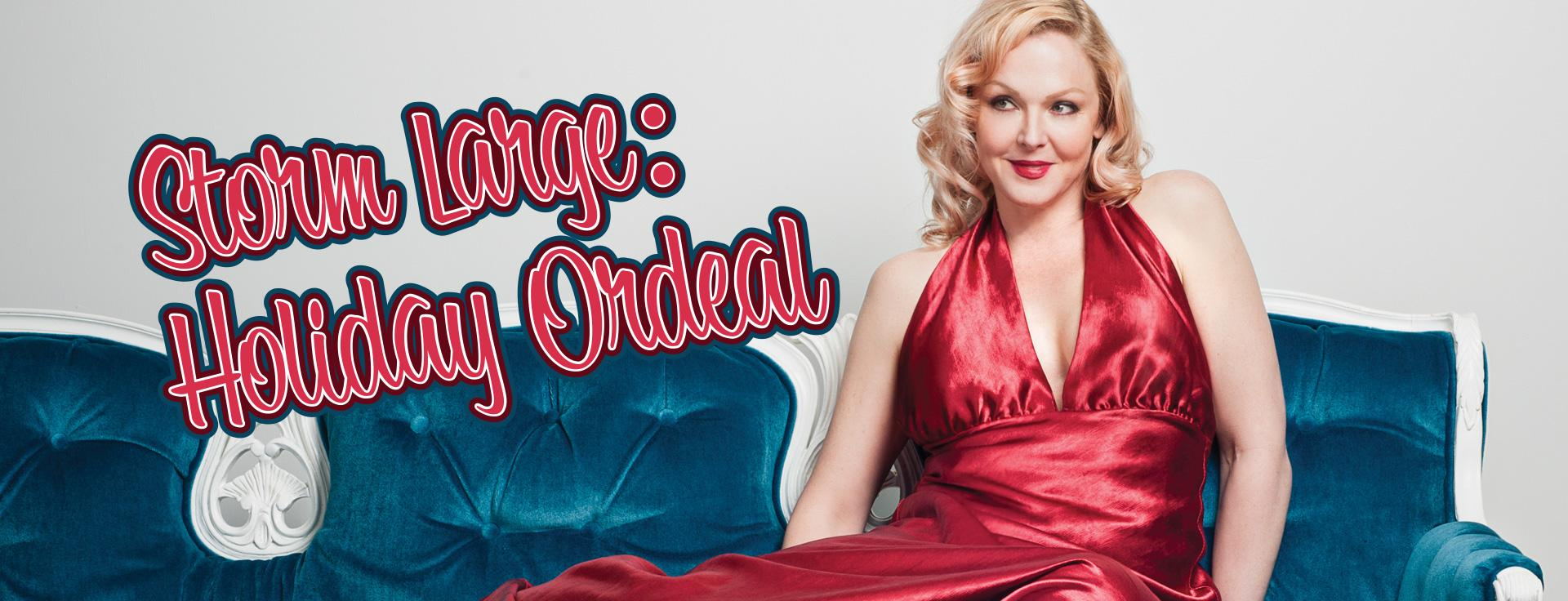 Storm Large in a silky red dress sitting on a blue couch
