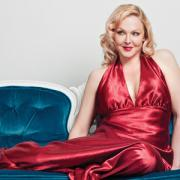 Storm Large in a silky red dress sitting on a old fashion couch